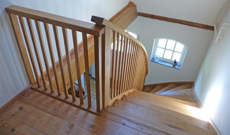 Trap met wrongstuk waarbij de leuning de helling van de trap volgt.
